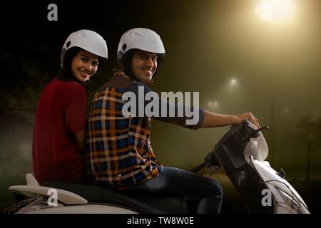 Allegro coppia giovane in sella a una moto di notte Immagini Stock