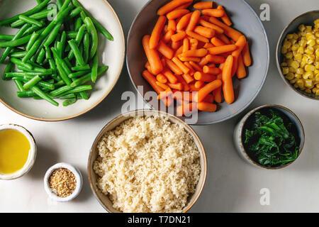 Il couscous con il riso parboiled verdure carotine, fagiolini, il mais dolce, spinaci nel separare le piastre in ceramica con semi di sesamo e olio di oliva. Vegan fo Immagini Stock