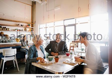 Senior i genitori e la figlia parlano in cafe Immagini Stock