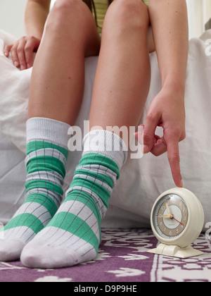 Donna in calze di lana di toccare sveglia Immagini Stock