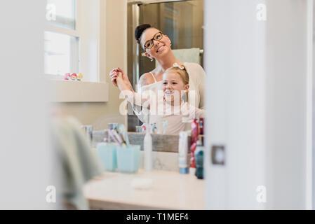 Sorridente madre e figlia nello specchio del bagno Immagini Stock