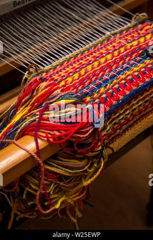 Regno Unito, Cumbria, York, Farfield Mill e colorati di tessitura su progressi sul telaio Immagini Stock