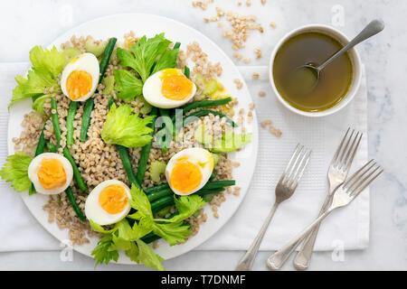 Fagiolo, orzo e insalata di uova con forche e una ciotola di medicazione. Immagini Stock