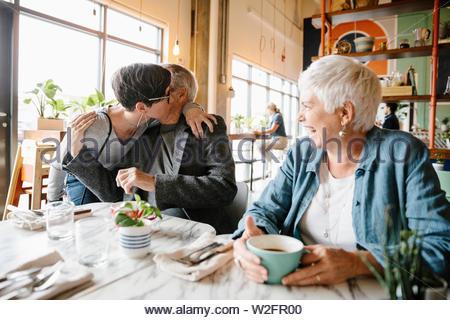 Figlia di saluto i genitori senior in cafe Immagini Stock