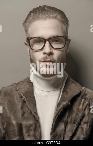 Ritratto in studio di un fresco giovane uomo con gli occhiali che indossa una giacca in pelliccia. Immagini Stock