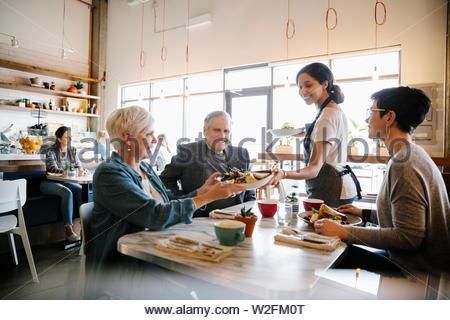 Cameriera di servire la famiglia in cafe Immagini Stock