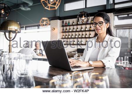 Imprenditrice lavora al computer portatile in bar Immagini Stock