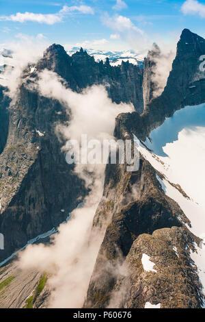 Vista aerea su montagne in valle Romsdalen, Møre og Romsdal, Norvegia. Il 3000 piedi verticale Parete Troll è parzialmente coperta dalla nebbia. Immagini Stock