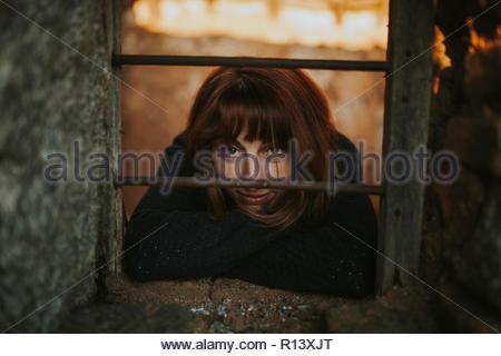 Ritratto di una donna che guarda attraverso una finestra nella fotocamera Immagini Stock