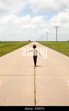 Ragazzo camminando lungo il marciapiede in paese Immagini Stock