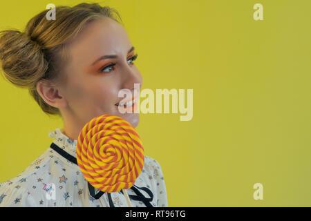 Close-up ritratto di una bellissima ragazza con brillante trucco e taglio di capelli divertente con un lecca-lecca su uno sfondo luminoso Immagini Stock