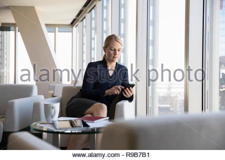 Imprenditrice utilizzando smart phone in office lounge Immagini Stock