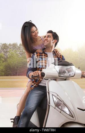Allegro coppia giovane in sella a una moto Immagini Stock