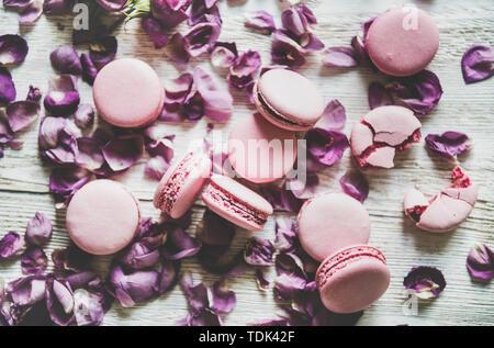 Rosa dolce macaron cookie e lilla boccioli di rosa e petali di fiori su un tavolo di legno sfondo, vista dall'alto, il fuoco selettivo. Food texture, sfondo e wallpa Immagini Stock