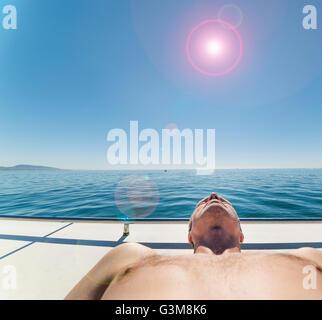 Uomo su una barca a vela per prendere il sole Immagini Stock