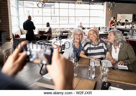 Le donne anziane amici che posano per una fotografia in ristorante Immagini Stock