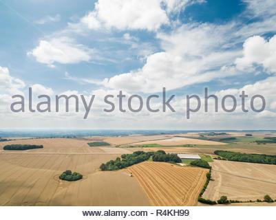 Paesaggio di raccolto antenna della mietitrebbia estate taglio campo di grano raccolto con rimorchio del trattore sotto il cielo blu in agriturismo Immagini Stock