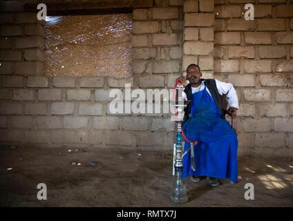 Beja uomo fumatori tubazione acqua, Mar Rosso Stato, Suakin, Sudan Immagini Stock
