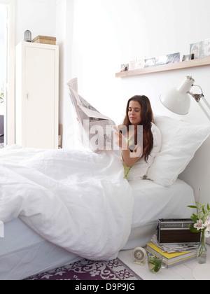 Bruna giovane donna leggendo il giornale in bed Immagini Stock