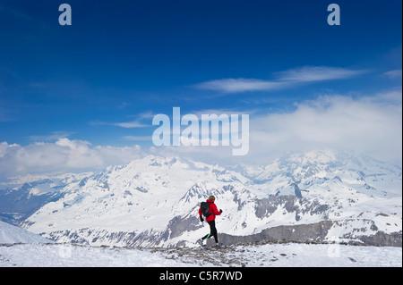 Esecuzione del pareggiatore tramite snowy mountain range. Immagini Stock