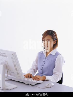 Donna che parla su un paio di cuffie con il computer Immagini Stock