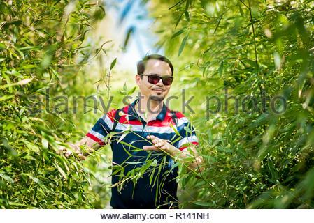 Ritratto di un giovane uomo che indossa gli occhiali da sole in piedi dalle piante Immagini Stock