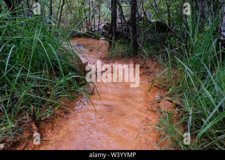 Sorgente di acqua Narzan molla con alto contenuto di Ferrum che dà un arrugginito di colore arancione lungo la riva del fiume Hasaut situato in Kabardino-Balkaria nel Nord Caucaso Distretto federale della Russia Immagini Stock