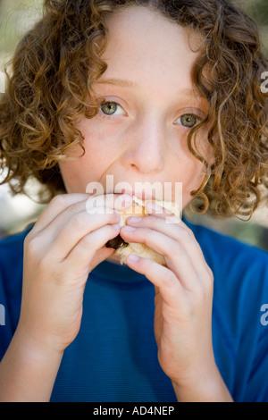 Un giovane ragazzo di mangiare una salsiccia in un rotolo di pane Immagini Stock
