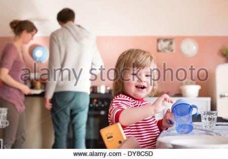 I giovani genitori la cottura di cibo per il loro bambino Immagini Stock