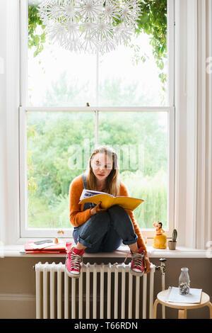 Focalizzato femmina giovane studente universitario che studia nella finestra Immagini Stock