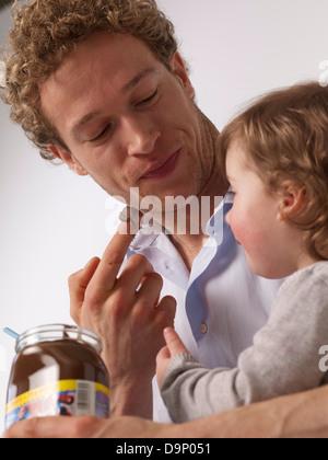 Padre e figlia di roditura cioccolato da spalmare Immagini Stock