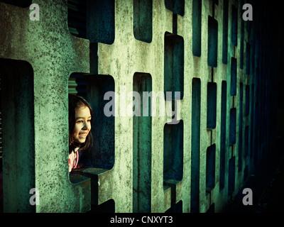Bambina sembra modellato attraverso il blocco di calcestruzzo parete Immagini Stock