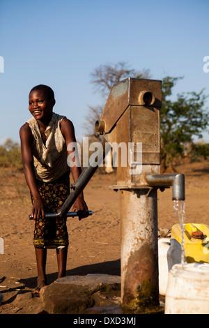 Africa bambino raccolta di acqua in un tubo di supporto Immagini Stock