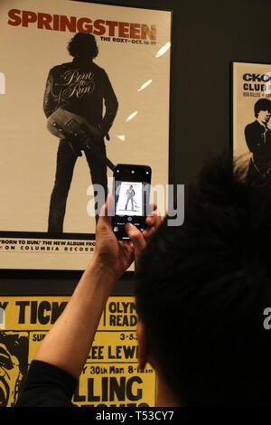 """Aprile 20, 2019 - New York, New York, Stati Uniti - Un museo goer prende una foto di BRUCE SPRINGSTEEN concerto poster sul display in """"Play forte: Strumenti di Rock and Roll' presentano presso il Metropolitan Museum of Art. (Credito Immagine: © Nancy Kaszerman/ZUMA filo) Immagini Stock"""