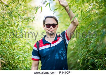 Ritratto di un giovane uomo che indossa gli occhiali da sole in piedi all'aperto Immagini Stock