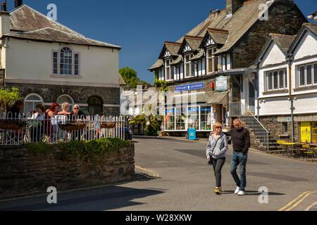 Regno Unito, Cumbria, Hawkshead, la piazza e i visitatori a piedi passato Peter Rabbit e amici shop negozio e clienti sat nella luce del sole al di fuori cafe Immagini Stock