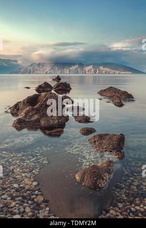 Straordinaria spiaggia tramonto con la montagna a distanza, e stelle sopra il cielo in Croazia Immagini Stock