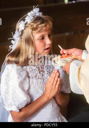 Ragazza giovane riceve la prima comunione nella Chiesa signor © Myrleen Pearson ....Ferguson Cate Immagini Stock
