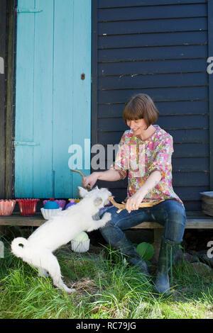 Donna che gioca con un cane Immagini Stock