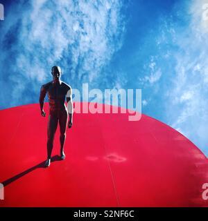 Una scultura di un uomo in piedi su un spazio rosso decora un monumento di un cuore rosso a Fatima, Portogallo Immagini Stock