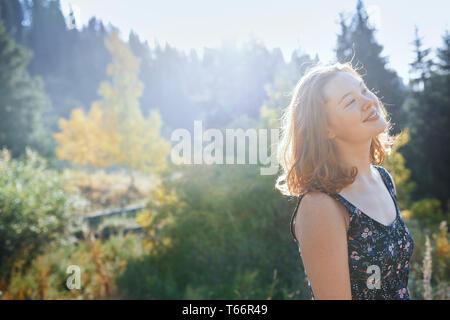 Ritratto di spensierata giovane donna nel soleggiato parco Immagini Stock