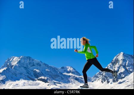Una donna jogging veloce sulla montagna innevata. Immagini Stock