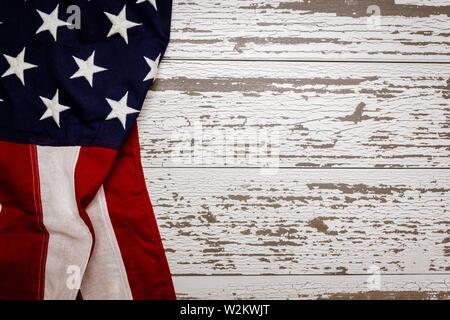 Un accartocciata bandiera americana su un listone bianco sfondo con copia spazio per vacanze ecc Immagini Stock