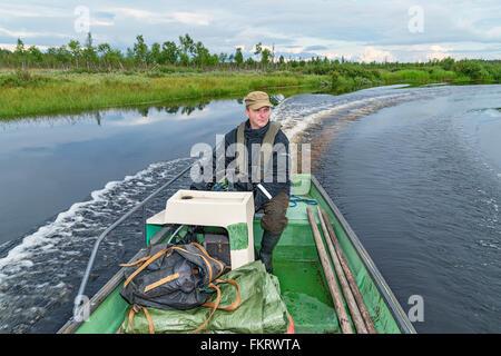 Spostamenti locali operatore trekkers il trasporto in barca a Urho Kekkonen national park, Lapponia, Finlandia. Immagini Stock