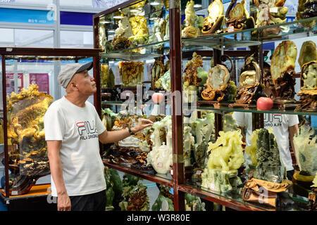 Harbin, la Cina della Provincia di Heilongjiang. 17 Luglio, 2019. Un visitatore richiede uno sguardo alla mostra durante la seconda Nordest Asiatico di cultura ed Arte Fiera di Harbin, capitale del nord-est della Cina di Provincia di Heilongjiang, 17 luglio 2019. Credito: Xie Jianfei/Xinhua/Alamy Live News Immagini Stock