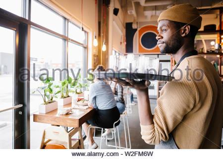 Server di sesso maschile che porta il vassoio di bicchieri in cafe Immagini Stock