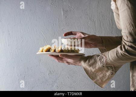Fritti gnocchi asiatici Gyozas potstickers su bianco Vassoio in ceramica e una ciotola di salsa di soia in mani femminili. Muro grigio a sfondo. Cena asiatica Immagini Stock