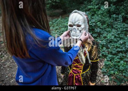 Una ragazza aiutando il suo amico con il suo costume per la notte di Halloween. Immagini Stock