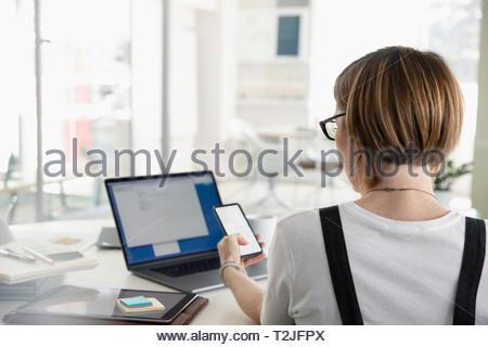 Imprenditrice utilizzando smart phone alla scrivania in ufficio Immagini Stock