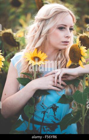 Bella giovane donna in un campo di girasoli a ora d'oro Immagini Stock